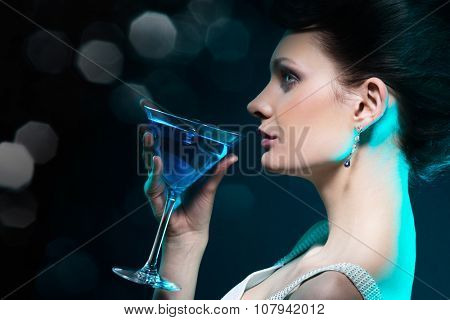 Young woman with martini glass in blue light on blured dark background