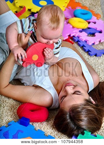 Kid baby boy with mother lying on floor and plying puzzle toy.