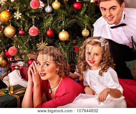 Family with little daughter dressing Christmas tree. Vintage style.