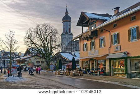 GARMISCH-PARTENKIRCHEN GERMANY - JANUARY 06 2015: People enjoying winter evening at sidewalk cafe in Garmisch-Partenkirchen (Germany). The tower of the St. Martin church visible in the background