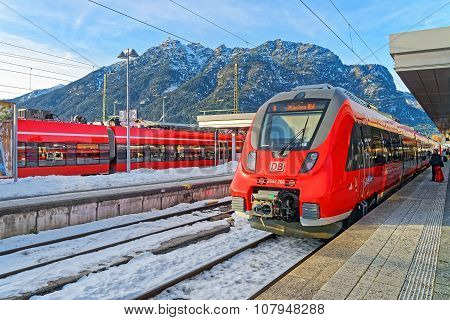 GARMISCH-PARTENKIRCHEN GERMANY - JANUARY 6 2015: Unidentified passengers with luggage waiting to board high-speed train at Garmisch-Partenkirchen railway station