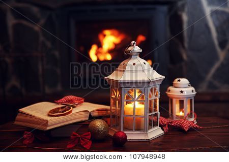 Book and candles on vintage wood table. Fireplace as background