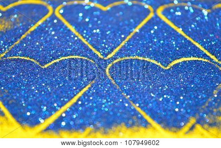 Blurry abstract background with hearts of blue glitter sparkle on yellow surface