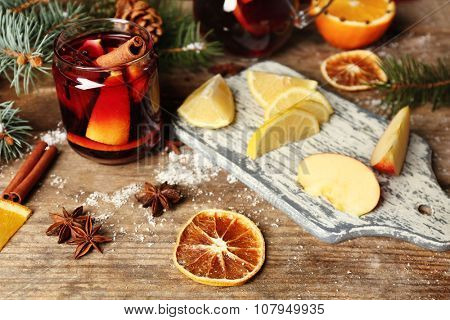 Mulled wine in glass bank with fruits on decorated wooden table