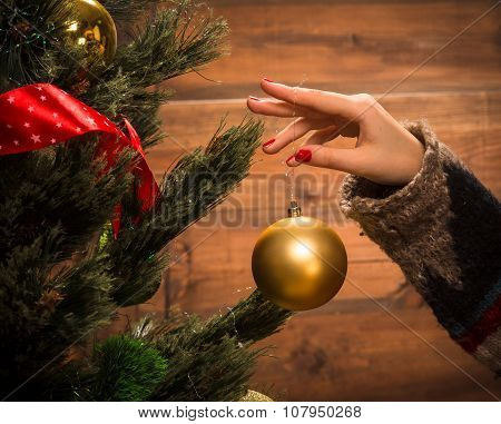 Girl decorating New Year tree with Christmas balls