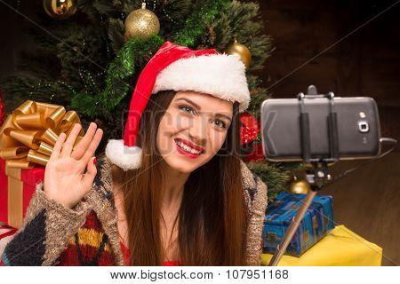Beautiful girl sitting near New Year tree and making selfies