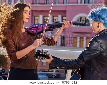 Women performer playing violin and guitar. Music street.