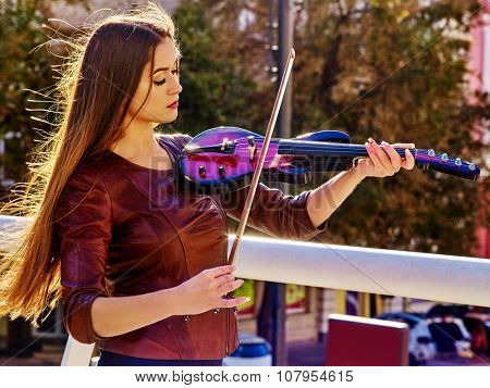 Woman performer playing violin alone. Music street.