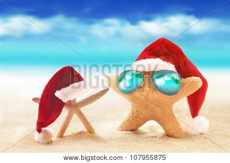 Starfish in sunglasses on summer beach and santa hat.