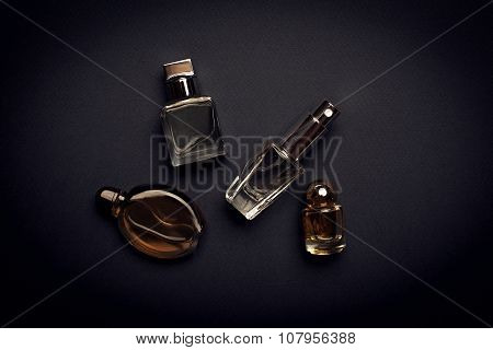 Different Perfume Bottles On The Dark Background