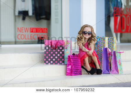 Little girl with shopping bags goes to the store