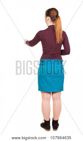 back view of young woman presses down on something. Isolated over white background. Rear view people collection. backside view of person. Low girl in a blue skirt right thumb presses the button.