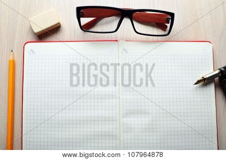 Opened checked notebook with eyeglasses and pen on wooden background, close up