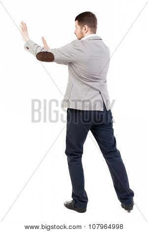 back view of business man pushes wall. Isolated over white background. Rear view people collection. backside view of person. A guy in a jacket hands in front of him.