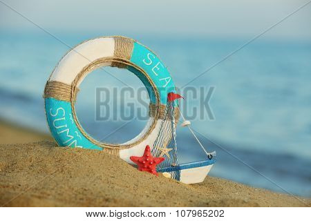 Beautiful life buoy in the sand with boat toy on unfocused sea background