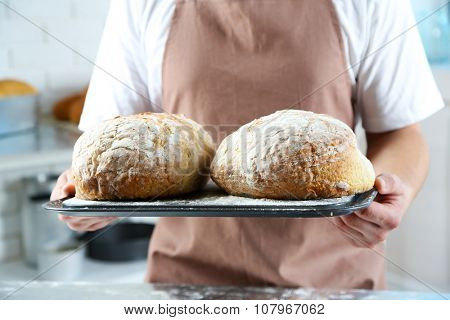 Baker checking freshly baked bread in kitchen of bakery