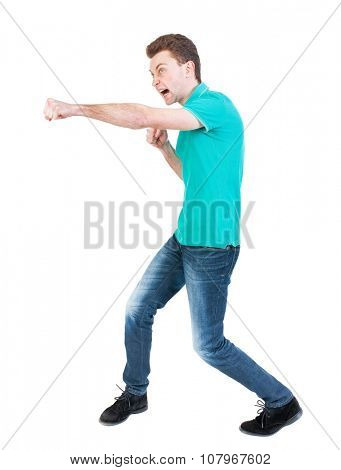 skinny guy funny fights waving his arms and legs. Isolated over white background. Funny guy clumsily boxing. Clumsily fighting man in a green jacket.