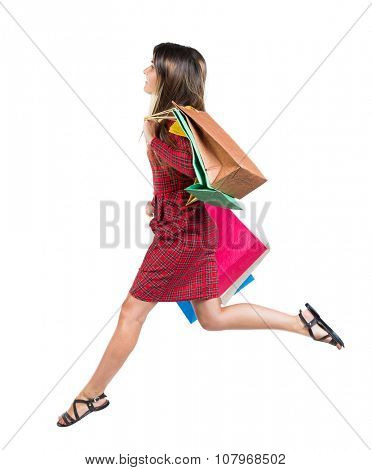 side view of a woman jumping with shopping bags. beautiful brunette girl in motion.  backside view of person.  Rear view people collection. Isolated over white background.