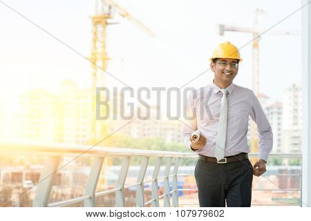 Asian Indian male site contractor engineer with hard hat holding blue print paper walking at construction site, crane with golden sunlight at the background.