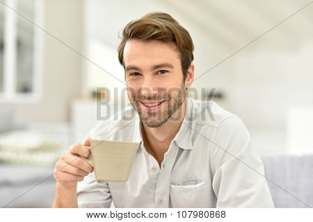 Portrait of handsome man at home, holding tea cup