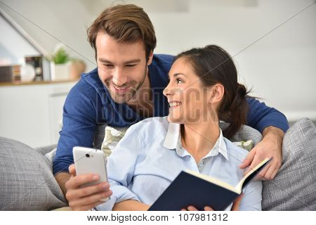 Couple at home entertaining and reading message on smartphone
