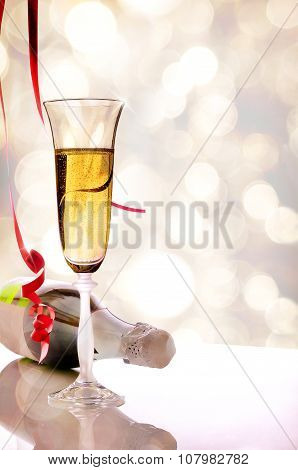 Glass Of Sparkling White Wine And Bottle On Table Vertical