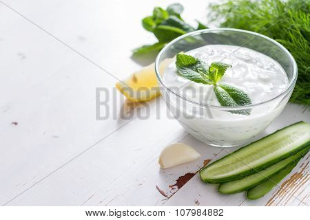 Tzatziki sauce ingredients, white wood background