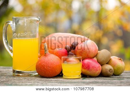 glasses of juice and lots of autumn fruits on wooden table, outdoor