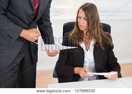 Businessman Showing Document To Employee