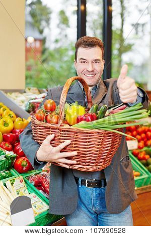 Happy man with fresh vegetables holding thumnbs up in a supermarket