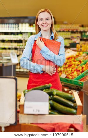 Young saleswoman in organic food store holding a clipboard