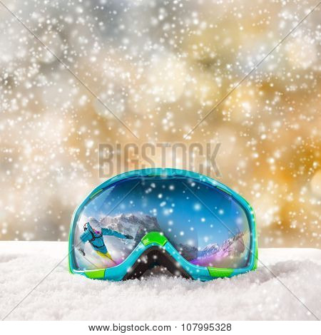 Colorful ski glasses with skier on snow. Winter ski theme.