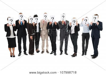 Business Team Hiding Faces With Question Mark Signs