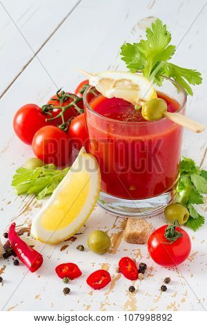 Bloody Mary ingredients on white wood background