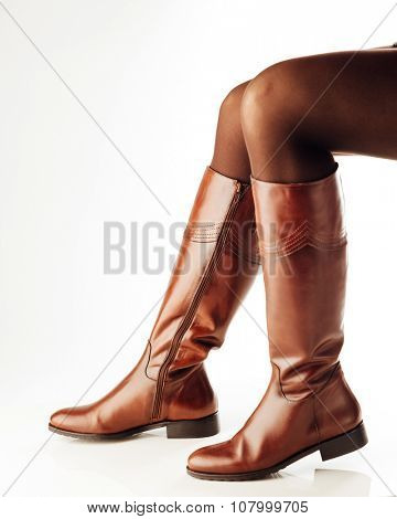 woman legs wearing brown leather high boots, white background
