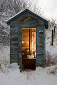 stock photo of outhouse  - Out house that is covered in snow and icicles - JPG