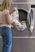 stock photo of washing machine  - Woman unloading clothes from dryer at laundromat - JPG