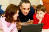 stock photo of computer technology  - father and children lying on the floor at home and looking into a portable computer - JPG