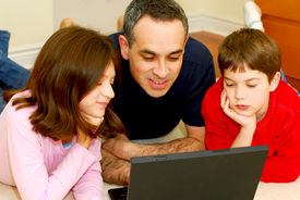 foto of computer technology  - father and children lying on the floor at home and looking into a portable computer - JPG