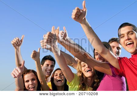 Happy group of joyful friends raising hands with thumb up sign against blue sky