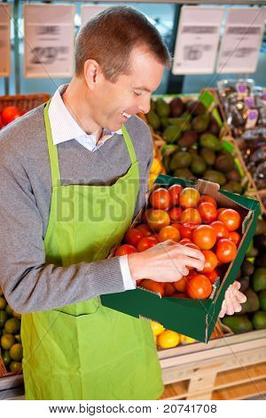 Happy market assistant holding box of tomatoes in the supermarket