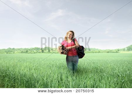 Smiling student standing on a green meadow