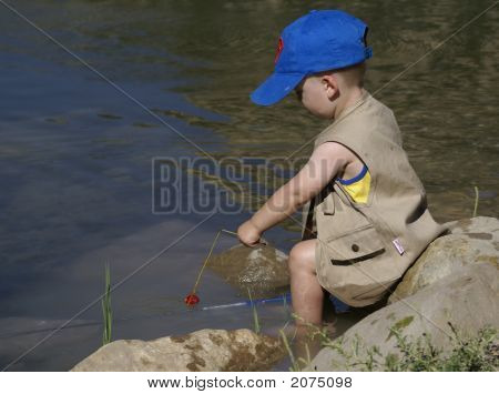 Small Boy Trying To Fish In Pond