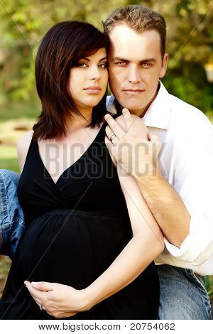 Expecting couple with eight months pregnant woman in the park