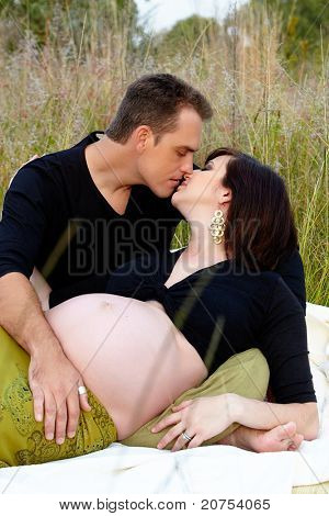 Pregnant couple with eight months pregnant woman wearing a black top and a green skirt kissing in the park, on a picnic.