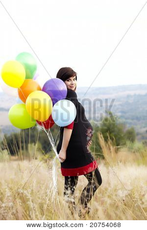 Beautiful eight months pregnant brunette woman wearing a black dress and holding a bunch of balloons standing outside in the tall grass .