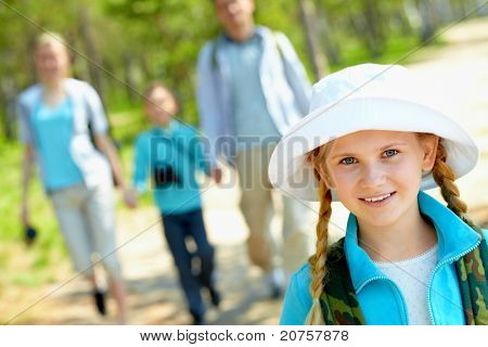 Portrait of pretty girl looking at camera with her family on background in summer