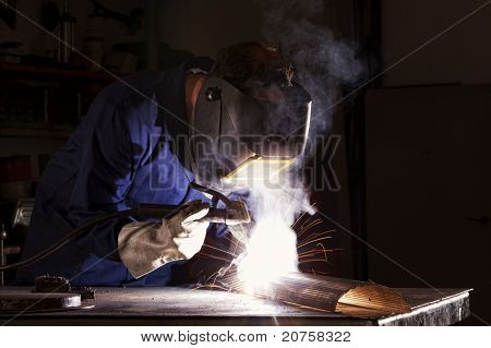 Soldador de electrodo industrial con visera y azul un pedazo de metal en el taller de soldadura en general.