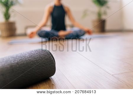 poster of Close up of rolled yoga mat in fitness center and blurred woman at the back in lotus yoga pose. Fitness mat on floor with woman practising yoga in background.