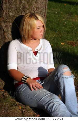 Blond Woman Sitting On Ground In Sun By Tree